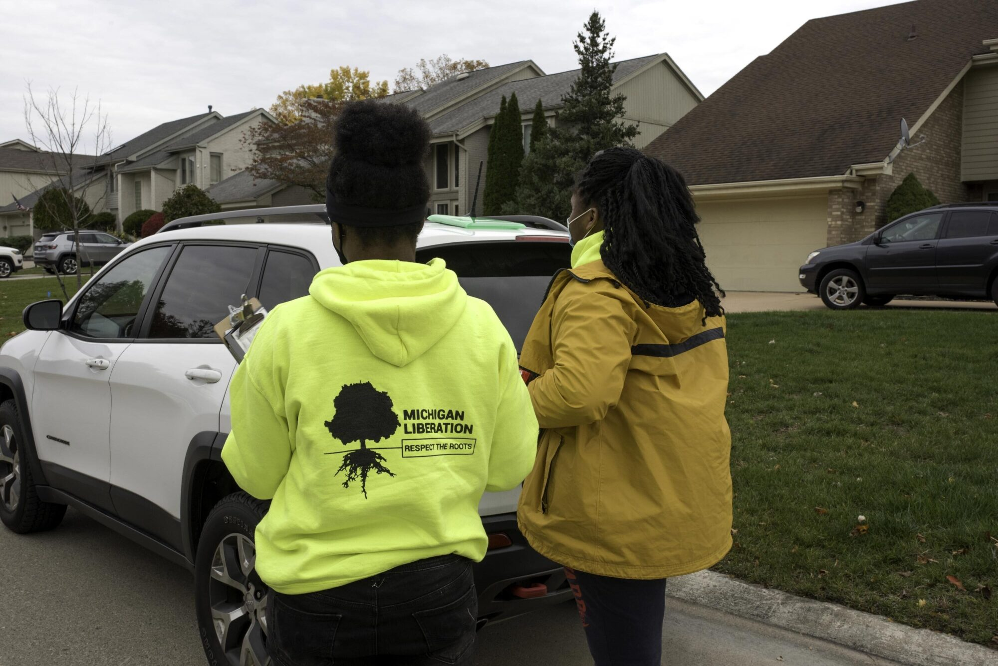 Two girls passing out campaign literature on a suburban street.